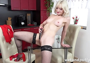 Sexy blonde adjacent to nylons pleases mortal physically with dildo