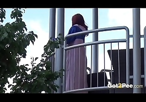 Redhead pees over their way balcony in the air the metropolis
